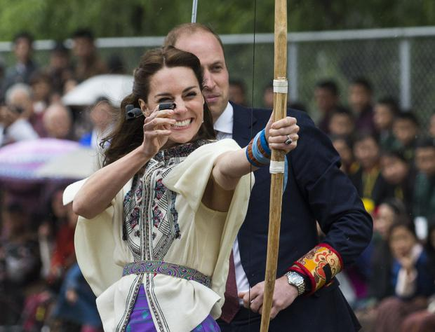 Britain's Catherine (L), the Duchess of Cambridge, fires an arrow as Prince William, Duke of Cambridge, looks on at the Changlingmethang National Archery ground in Thimphu during their visit to Bhutan on April 14, 2016. / (Photo: ROBERTO SCHMIDT/AFP/Getty Images)