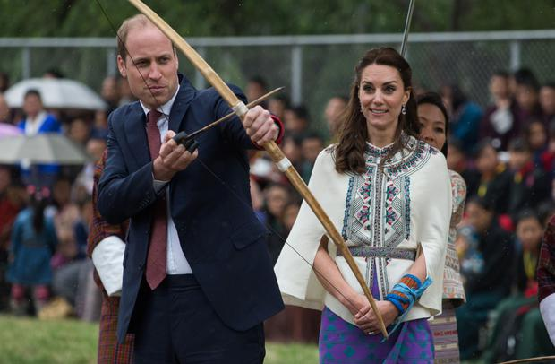 TOPSHOT - Britain's Catherine, Duchess of Cambridge(R)looks on as she watches Prince William, Duke of Cambridge prepare to fire an arrow at The Changlingmethang National Archery ground in Thimphu on April 14, 2016. (Photo ROBERTO SCHMIDT/AFP/Getty Images)
