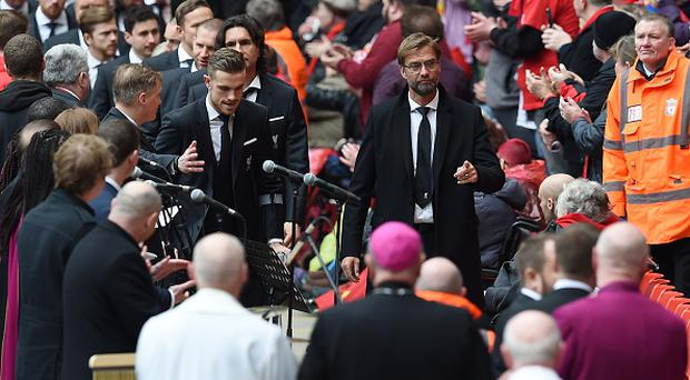Liverpool's German manager Jurgen Klopp (centre R) arrives with his players to attend a memorial service at Anfield in Liverpool, north west Engand on April 15, 2016, on the 27th anniversary of the Hillsborough Disaster. 96 Liverpool supporters died at the 1989 FA Cup semi-final between Liverpool and Nottingham Forest at the Hillsborough football ground in Sheffield, northern England. 2016 will be the final year a memorial service is held at Anfield. / AFP / PAUL ELLIS (Photo credit should read PAUL ELLIS/AFP/Getty Images)