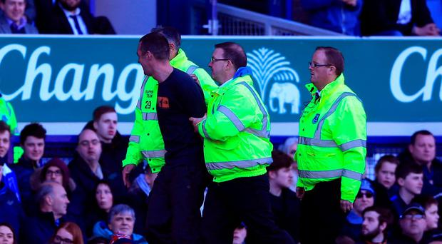 A pitch invader is led away by stewards during the Barclays Premier League match at Goodison Park