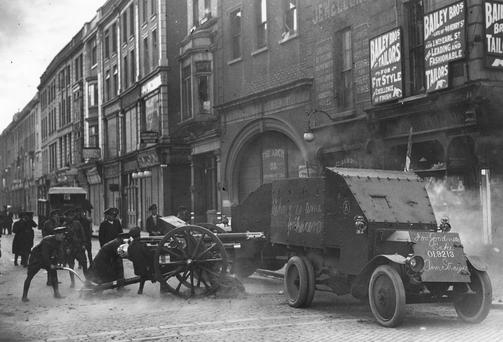 Gunning for each other: (circa 1922) Uniformed Free-State troops fire an 18-pounder field gun from the top of Henry Street, Dublin, at republican targets in the Gresham Hotel, during the Irish Civil War. A Lancia armoured car is in the foreground Photo: Hulton Archive/Getty Images