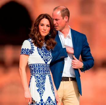 The Duke and Duchess of Cambridge stand after posing for a photo on a bench at the Taj Mahal. Photo: Dominic Lipinski/PA Wire