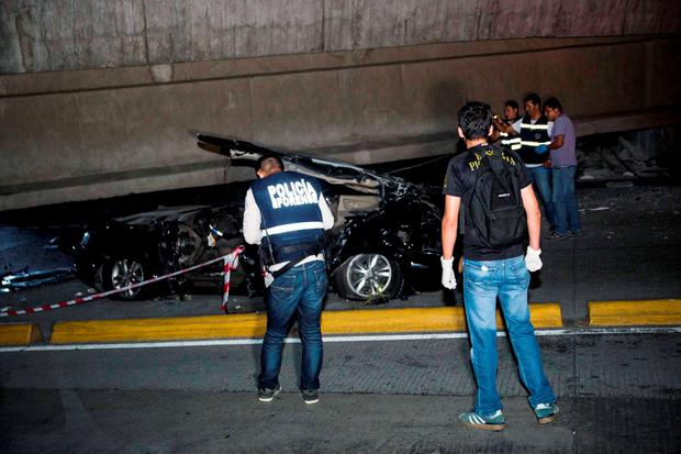 Police look at a car crushed under a collapsed overpass in Guayaquil, Ecuador, Saturday April 16, 2016. The strongest earthquake to hit Ecuador in decades flattened buildings and buckled highways along the country's coast, killing at least 41 people and causing damage hundreds of miles (kilometers) away from the epicenter in the capital and other major cities.(AP Photo/Jeff Castro)
