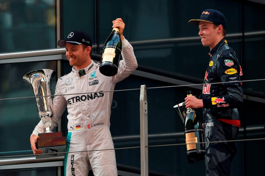 Mercedes AMG Petronas F1 Team's German driver Nico Rosberg (L) celebrates on the podium after winning the Formula One Chinese Grand Prix, as third-placed Red Bull Racing driver Daniil Kvyat of Russia (R) looks on, in Shanghai on April 17, 2016. / AFP PHOTO / GREG BAKERGREG BAKER/AFP/Getty Images