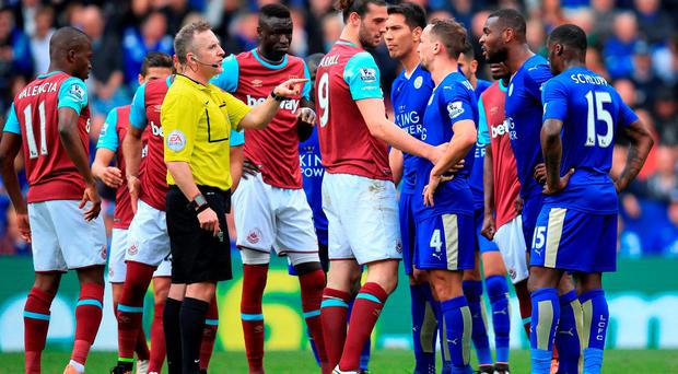 Match referee Jonathan Moss awards a penalty to Leicester City after a foul by West Ham United's Andy Carroll (centre)