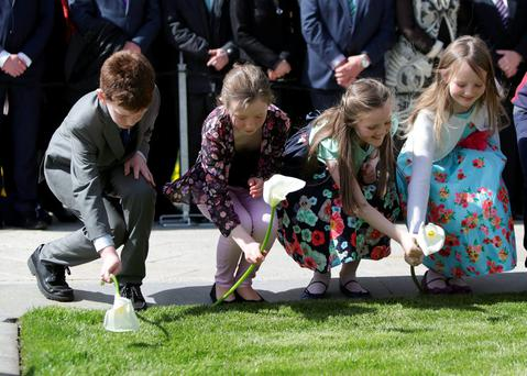 David McGovern (10), Caoimhe Maloney (10), Eabha Gormley (8) and Ruth Gormley (9) place easter lilies on the graves at the 1916 commemoration at Arbour Hill yesterday. Photo: Damien Eagers