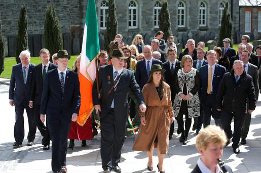 Niall McEneaney and Anthony Greene holding the Tricolour, and Emma Murphy leading Fianna Fáil's Micheál Martin and party members at the 1916 commemoration at Arbour Hill yesterday. Photo: Damien Eagers