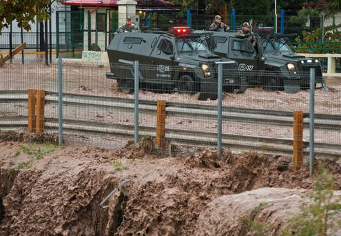 Two police armored vehicles stand in a flooded street due heavy rains in Santiago, Chile. (AP Photo/Esteban Felix)