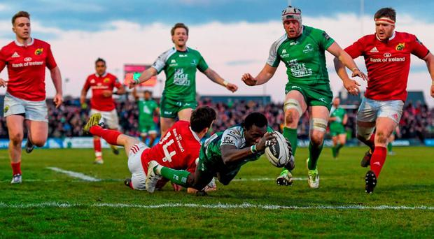 Niyi Adeolokun goes over to score Connacht's third try despite the efforts of Munster's Darren Sweetnam during Saturday's game at The Sportsground. Photo: Stephen McCarthy / Sportsfile