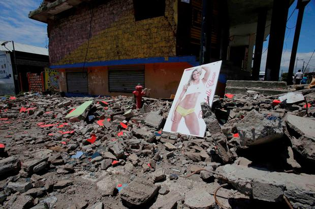 An advertisement for nutritional supplements stands amid the debris left behind by an earthquake in Pedernales, Ecuador, Sunday, April 17, 2016