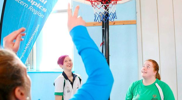Athletes Sarah Byrne from Clondalkin and Laura Reynolds from Wicklow watch a prisoner take a a shot at the basket in the Dochas Centre. Photo: Marc O'Sullivan