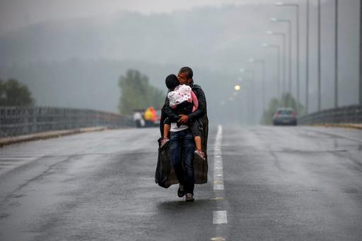A Syrian refugee kisses his daughter as he walks through a rainstorm towards Greece's border with Macedonia, near the Greek village of Idomeni in September. President Higgins has criticised the response of Europe to the refugee crisis, describing it as being characterised by 'ruinously narrow self-interest'. REUTERS/Yannis Behrakis
