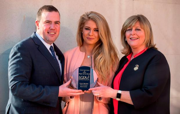 UCD's Ciara Murphy receives the LGFA Player of the Month award for March from Sean Reid, Deputy General Manager of The Croke Park Hotel, and LGFA president Marie Hickey. Photo: Sportsfile