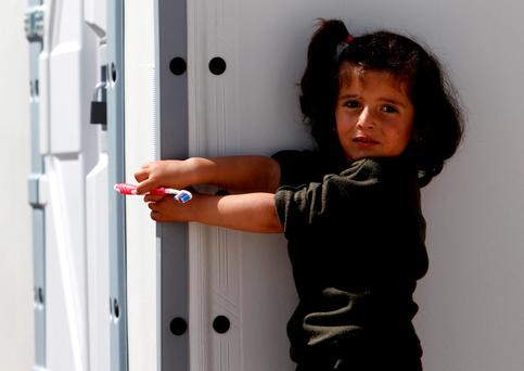 A refugee girl holding a tooth brush stands in front of a tent at the transit centre for refugees, near the southern Macedonian town of Gevgelija, near the border with Greece. Photo: AP