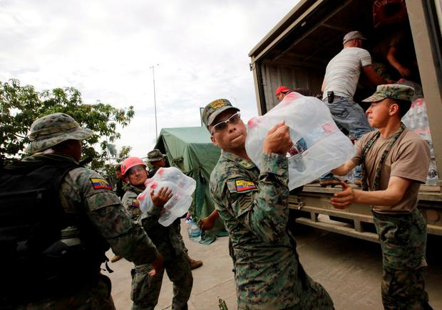 Soldiers carry water from a truck after an earthquake struck off the Pacific coast, in the town of Canoa, Ecuador, April 18, 2016