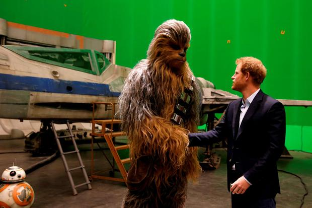 Prince Harry (R) meets Chewbacca during a tour of the Star Wars sets at Pinewood studios on April 19, 2016 in Iver Heath, England. (Photo by Adrian Dennis-WPA Pool/Getty IMages)