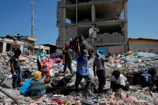 Residents try to recuperate some of their belongings buried in the rubble on a neighborhood block that was destroyed by the earthquake in Pedernales, Ecuador, Tuesday, April 19, 2016. (AP Photo/Dolores Ochoa)