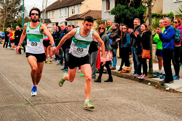 Raheny Shamrock's Mick Clohisey (l) hands the baton over to Daire Bermingham on the final leg to winning the Senior Men's relay race at the The Glo Health AAI National Road Relays in Raheny, on Sunday. Pic: Sportsfile
