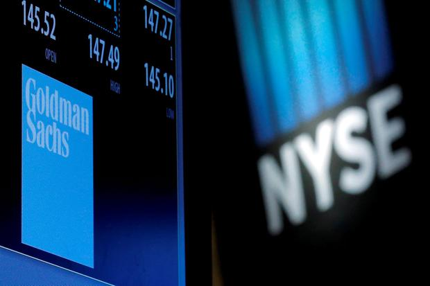 A screen displays the ticker symbol and information for Goldman Sachs on the floor of the New York Stock Exchange (NYSE)
