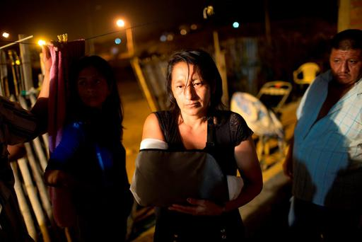 Edith Mero nurses her broken arm as she stands in front of her collapsed house in Estancia Las Palmas, Ecuador. (AP Photo/Rodrigo Abd)