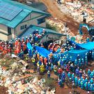Rescuers, usuing blue plastic sheet, search for missing persons at the site of a landslide in Minamiaso, Kumamoto prefecture, Japan. (Yohei Fukai/Kyodo News via AP)