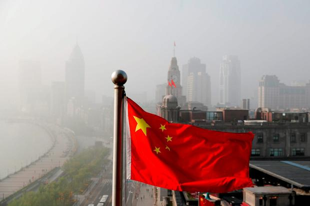 A Chinese national flag flutters against the office buildings at the Shanghai Bund shrouded by pollution and fog in Shanghai, China. (AP Photo/Andy Wong)
