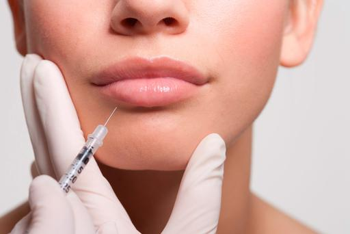 Close up of woman receiving Botox injection in lips. Stock picture