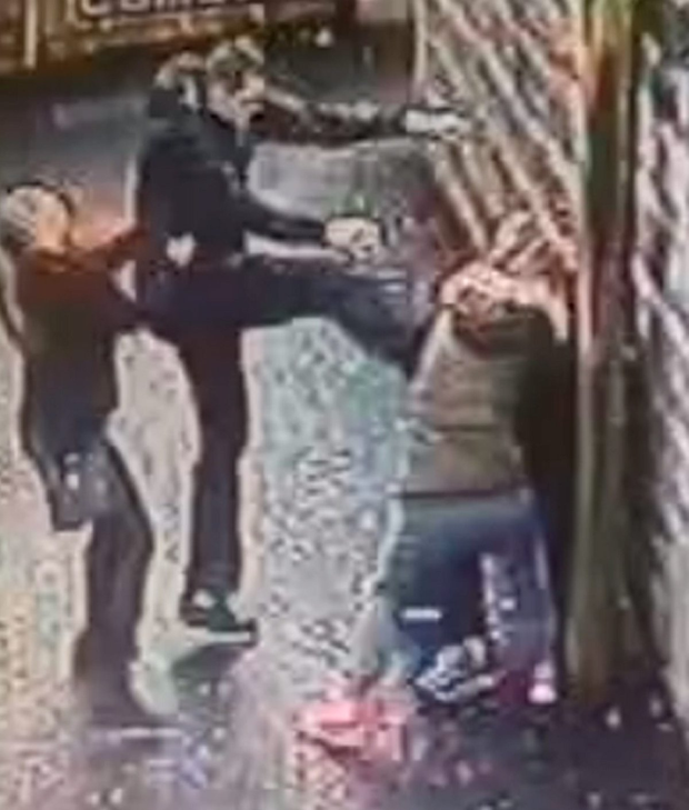 4) The man's attacker launches a series of brutal kicks as a woman tries to stop the attack