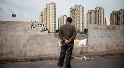 A man gazes at residential buildings in the distance in the Jiading district of Shanghai, China. The country's economy is six times as large as it was 30 years ago. Photo: Qilai Shen/Bloomberg