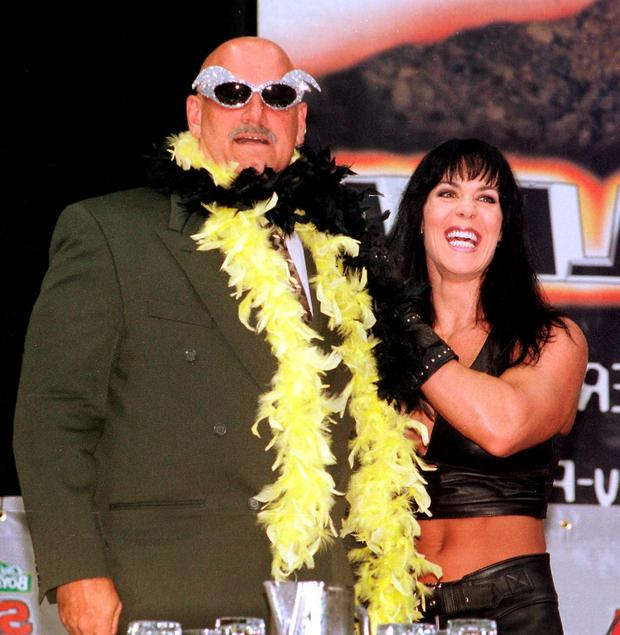 Minnesota Governor and former professional wrestler Jesse Ventura (L) is adorned with his former trademarks, sequined sunglasses and a feather boa, by wrestler Chyna