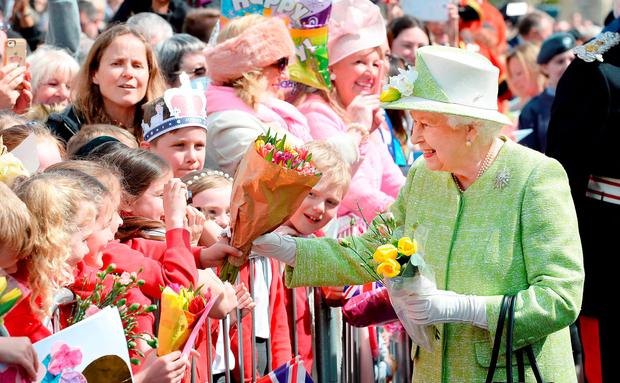 Britain's Queen Elizabeth II greets well-wishers on her 90th birthday in Windsor, England; inset left: a royal fan waits in the crowd. Photo: AFP/Getty Images