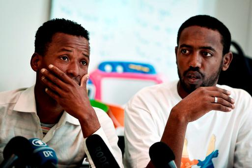 Survivors of a deadly shipwreck, Mowlid Isman of Somalia (left) and Muaz Mahmud Aymo of Ethiopia react during a press conference in Athens yesterday. Photo: AFP/Getty