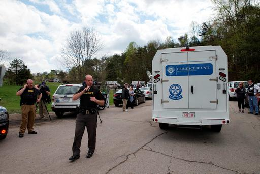 Authorities allow crime scene investigation vehicles to pass a perimeter checkpoint near a crime scene, Friday, April 22, 2016, in Pike County, Ohio. (AP Photo/John Minchillo)