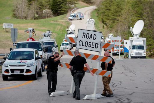 Authorities set up road blocks at the intersection of Union Hill Road and Route 32 at the perimeter of a crime scene, Friday, April 22, 2016, in Pike County, Ohio. (AP Photo/John Minchillo)