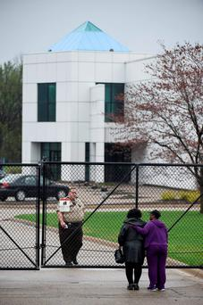 Two onlookers stand outside the gates of Paisley Park, Prince's estate in Chanhassen, Minnesota. Photo: Reuters