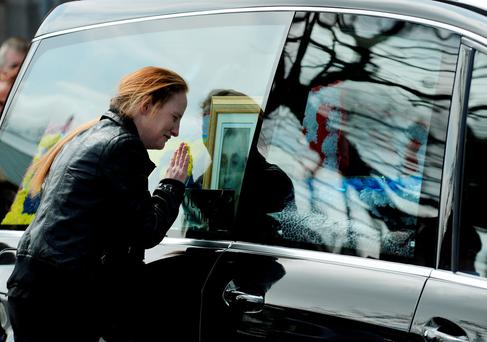 Angeline Power looks at a picture of her late fiancé Martin through the hearse window after the funeral in Dublin, which was attended by Taoiseach Enda Kenny. Photos: Caroline Quinn