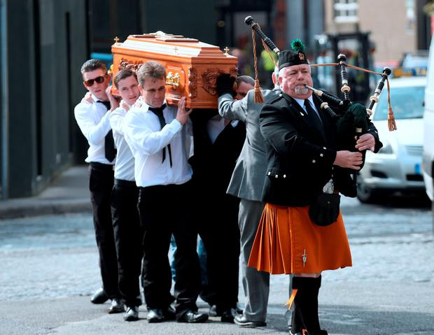 The coffin of Martin O'Rourke is carried to St Michan's Church accompanied by a piper. Photo: Caroline Quinn