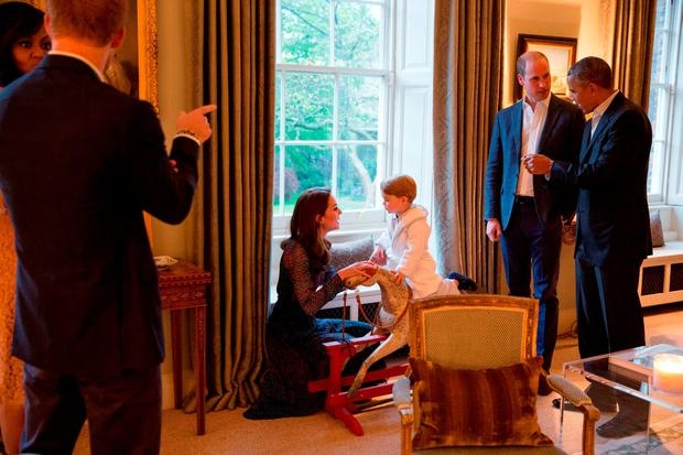 Obama chats with Prince William while Kate Midleton plays with Prince George as the First Lady Michelle Obama talks to Prince harry. Photo: Kensington Palace/Pete Souza/White House Photographer/PA Wire