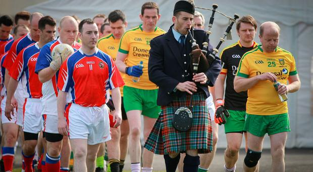 Captains Mark O'Brien and Shaun Campbell are led out by piper Stephen Byrne. Photo Brian McDaid