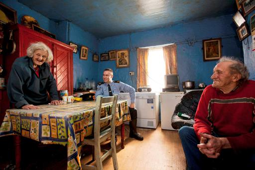 Sergeant Fergus Gaughan visiting brother and sister Nora and Tomás Ó Máille at their home Photo: Mark Condren