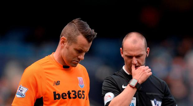 Stoke City's Irish goalkeeper Shay Given (L) talks with referee Robert Madley as they walk off at half time during the English Premier League football match between Manchester City and Stoke City at the Etihad Stadium