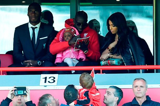 Liverpool's Mamadou Sakho (top centre) signs a programme for a fan in the stands sitting next to Liverpool's Zaire-born Belgian striker Christian Benteke). The French defender is being investigated by UEFA over a possible anti-doping rule violation. Photo: Paul Ellis/AFP