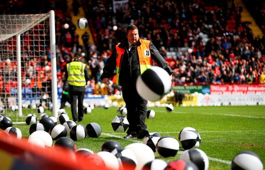 A steward attempts to clear balloons thrown onto the pitch at kick-off during the Sky Bet Championship match between Charlton Athletic and Brighton and Hove Albion at The Valley yesterday