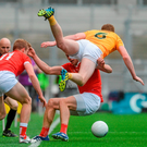 Louth duo James Stewart and Jim McEnaeney send Antrim's Martin Johnson into the air in the Allianz NFL Division 4 final Photo: Sportsfile