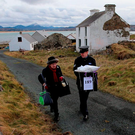 Presiding Officer Carmel McBride and Gda Sgt Paul McGee carry a ballot box on Inishbofin during the election Photo: Niall Carson/PA