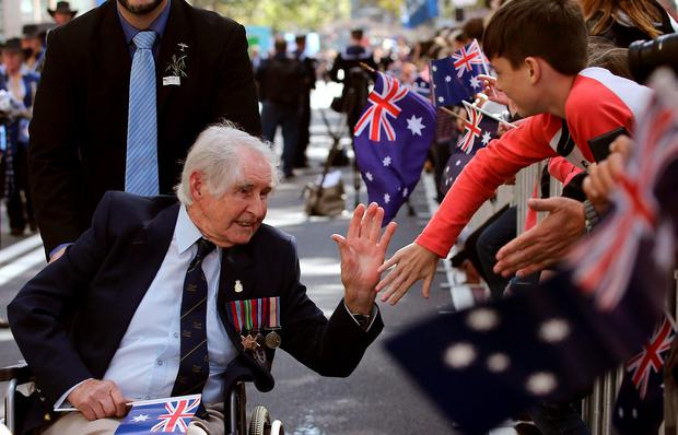 A war veteran gives a high five to a boy as he participates in the annual Australia and New Zealand Army Corps (ANZAC) parade in Sydney, Australia, Monday, April 25, 2016. ANZAC Day began as a commemoration of the landing of Australian and New Zealand troops in Gallipoli in 1915 but has evolved into a National day of remembrance for all who served and died in all wars, conflicts, and peacekeeping operations. (AP Photo/Rob Griffith)