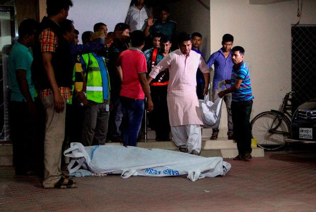 The bodies of two gay rights activists who were hacked to death are brought down from an apartment in Dhaka on April 25, 2016. Photo: AFP/Getty Images