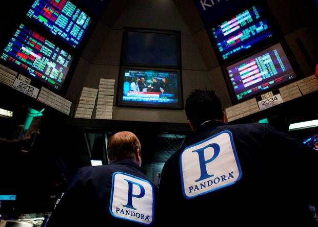 Traders work at the kiosk where Pandora internet radio is traded on the floor of the New York Stock Exchange. Photo: Reuters