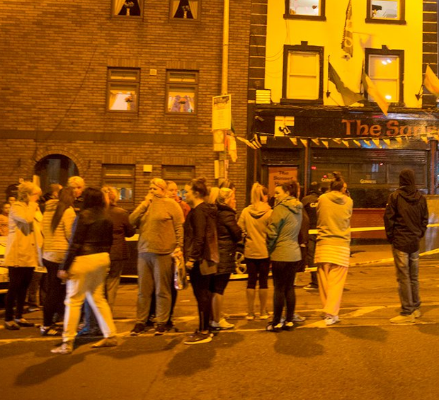 Distressed members of the public gather at the scene of the shooting at the Sunset House