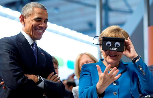 U.S. President Barack Obama looks on as GermanChancellor Angela Merkel tests VR goggles when touring the Hannover Messe, the world's largest industrial technology trade fair, in Hannover. Photo: AP